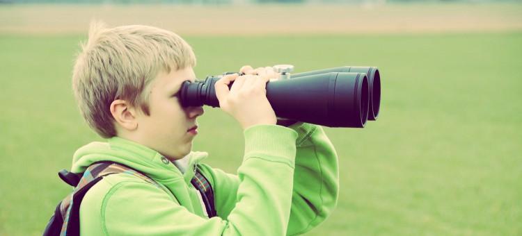 Niño con prismáticos emulando la investigación de la competencia