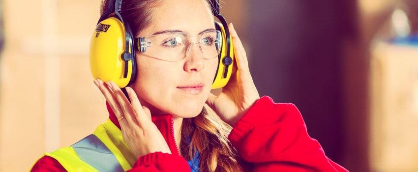 Chica con mono de trabajo y gafas protectoras. Seguridad en el trabajo